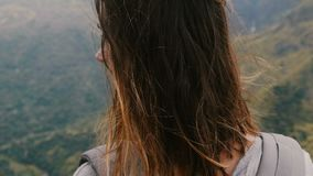 Close-up camera moves round young relaxed woman with backpack enjoying wind blowing in hair at epic mountain scenery. Close-up camera moves round relaxed woman stock video footage