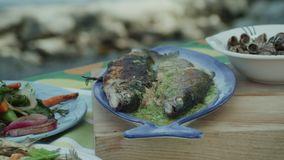 Close up, camera pan of fried Salmo ohridanus. Belvica, Ohrid trout, snails and vegetables onions, green peppers, carrots, chard leafs, garlic. Freshwater stock video footage
