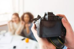 Close up of camera that is ready to take a picture of two beautiful girls. Somebody`s hands are hold it. Close up of camera that is ready to take a picture of royalty free stock image