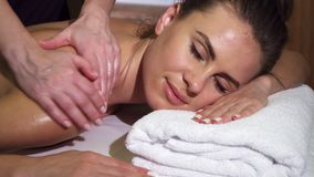 Close-up shows the relaxed face of a girl who is having a back massage stock image
