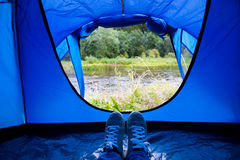 Close up of camper legs lying near tent entrance Stock Images