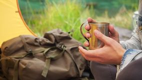 Man hands holding iron mug at travel tent on field