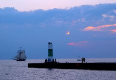 Romantic Lake Michigan. A beautiful pink and blue evening sky sits over a romantic looking scene in Lake Michigan. A ship sails by, while a pier holds people stock photo
