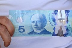 A close up of Canadian money- $5.00 bill. Canadian $5.00 currency. This picture can be used as a magazine front cover or billboard for anything to do with money royalty free stock images