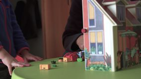 Candid child and dad playing with dollhouse close up SF. Close up of Candid child and dad are playing at home with a dollhouse joking and smiling stock video footage