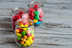 Close-up of candies in glass jars. Three jars with colorful candies and sweets on wooden table Royalty Free Stock Images