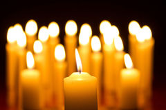 Close-up of candle with many candles bokeh in the background Royalty Free Stock Image