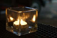 A candle burning in a crystal support stock photos