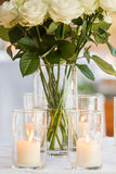 Close-up of candles. A whole bunch of roses in a pot on a table with candles Stock Images