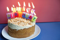 Close-up of candles burning on birthday cake over colored background Royalty Free Stock Photos