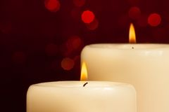 Close-up of candles with flame on red bokeh Stock Photography