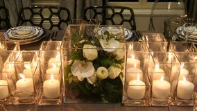 Close up of flower decor and candles on the dinner table royalty free stock image