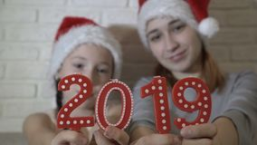 Close-up, candles in the form of numbers 2019 in the foreground. Children in the hats of Santa Claus holding red numbers. Symbol of new year. Blurred stock video footage