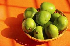 Cane bowl with raw mango fruit. Close up of cane bowl with raw mango fruit in sunlight Stock Photos