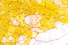 Close up of cannabis oil concentrate aka shatter isolated agains. Close up of cannabis oil concentrate aka shatter on top of net pattern isolated against white Royalty Free Stock Image