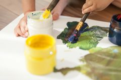 Close-up of cans with paints, brushes and children`s hands. stock photo