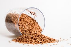 Close up. Capacity for spices lies near a pile of flax seeds. White background. Copy space