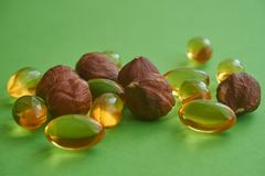 Close up capsules and nuts on green background. Close up golden color oil capsules and nuts on green background, health care, diet, weight loss, healthy stock photo