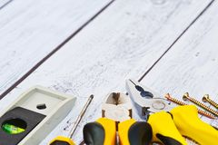 Close-up captured construction tools set. Some construction hand tools on the working desk - pliers, nippers, level tool, screwdriver with screws. Honest work Stock Images