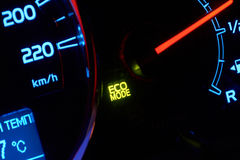 Close up of car dashboard with green hybrid mode icon on. Royalty Free Stock Image