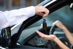 Close up of car dealer giving keys to woman stock photography
