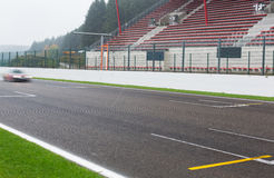 Close up of car driving on speedway track or road. Motosports, weather, extreme and race concept - close up of car driving on speedway track or road and stands Stock Photos