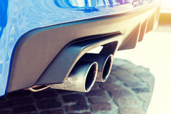 Close up of a car dual exhaust pipe in sunlight Stock Images