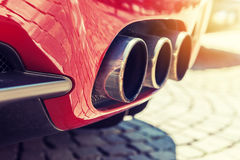 Close up of a car dual exhaust pipe in sunlight Royalty Free Stock Images