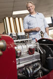 Close up of car engine with happy senior man standing behind Stock Photography