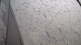 Close-up, on the car glass windows rain drops drip down a multitude of streams. it`s raining heavily, downpour.  stock footage