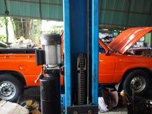 Close up car lifting in garage. Auto repair service Stock Photo
