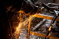 Close up of car mechanic hands welding grinding machine.Sparks of grinding machine while cutting car exhaust pipe.  royalty free stock image