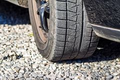 Close up of car& x27;s winter tyre tread on the gravel road.  Royalty Free Stock Images