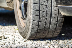 Close up of car& x27;s winter tyre tread on the gravel road Stock Photo