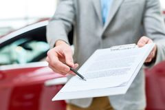 Close Up Car Salesman Handing Contract to Client. Close up view  portrait of unrecognizable car salesman handing purchase contract to client buying brand new car Royalty Free Stock Photography