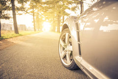 Close up on a car tyre while drifting on a street. Sport car driving fast on the street Royalty Free Stock Images