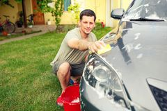 Close up of car washing. Male cleaning car using sponge and foam. Close up of car washing. Smiling male cleaning car using sponge and foam in the house yard Stock Image