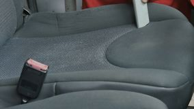Worker clean passenger seat with vacuum cleaner. Close-up. Car washman cleans the interior of automobile. Worker uses vacuum cleaner to clean the cabin of car stock video footage