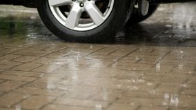 Close-up of a car wheel, cars are wetted in parking lot, large drops fall with splashes into puddles, there is heavy. Rain, downpour, the whole parking lot is stock video footage