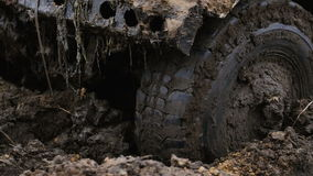 Close-up of a car wheel stuck in the mud. Wheel is spinning, but it helpless.  stock footage