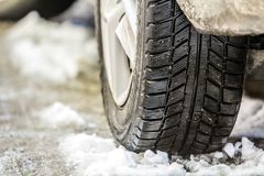 Close-up of car wheel in winter tire on snowy road Stock Images