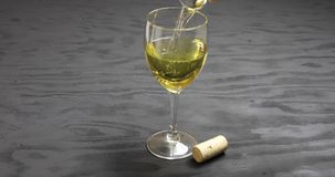 Close up of white wine pouring into glass stock video footage