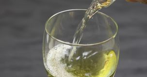 Close up of white wine pouring into glass stock video
