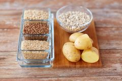 Close up of carbohydrate food. Diet, cooking, culinary and carbohydrate food concept - close up of grain and beans in glass bowls with potatoes on table stock photos