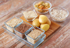 Close up of carbohydrate food. Diet, cooking, culinary and carbohydrate food concept - close up of grain, cereals in glass bowls and potatoes on table royalty free stock photos