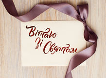 Close up of card note with brown ribbon on white background and words happy holiday Ukrainian Royalty Free Stock Images