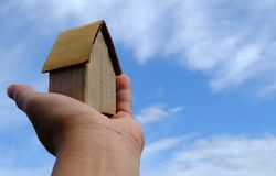 Cardboard House in Hand with Blue Sky Background. royalty free stock photos