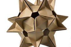 Close up on cardboard ornament. Intricate shape of figure, looking like a celestial body. Paper folding craft project stock photos