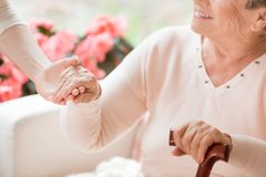 Close-up of caregiver supporting smiling senior woman with walki. Close-up of caregiver supporting smiling senior women with walking stick stock image