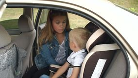 Closeup of a mother fastens her little son`s seat belts in a car seat in the car. Close-up of a caring mother fastens her little son`s seat belts in a car seat stock video